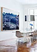 Designer dining area with long table, classic chairs, cylindrical lampshade and large photo of Roman Forum