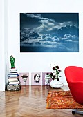 Collection of artworks in corner with small ceramic sculpture and modified portraits from flea market below photo of dramatic sky