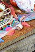 Vintage-Teegeschirr und chinesisches Porzellan mit herbstlicher Laubdekoration in rustikalem Ambiente