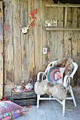 Rustic cabin wall decorated with antlers and weathered wooden crate as tea table next to comfortable wicker chair with cosy sheepskin blanket