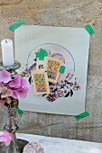 Delicate collage of nostalgic motifs fixed on concrete wall with washi tape; silver candlestick with hydrangea flowers