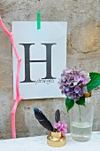 Letter H printed on paper on concrete wall behind hydrangea in cocktail shaker, feather and painted branch
