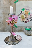 Hydrangea florets threaded on silver wire and seashell decorating patinated candlestick; nostalgic collage in background