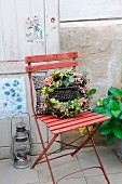 Autumnal wreath of vines, hydrangea flowers and acorns on garden chair with studded cushions; old door with nostalgic botanical prints in background