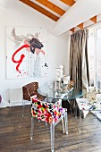 Designer, plexiglass chairs with patterned covers around glass table; modern painting on wall
