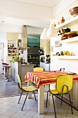 Small dining area with yellow vintage chairs in large kitchen-dining room with breakfast bar in background