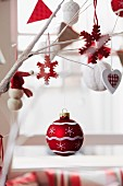 Red and white Christmas decorations hanging from branches with window in blurred background