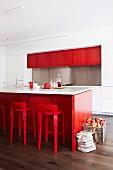 Apfelkiste und Tasche auf Boden neben Kücheninsel aus rot gefärbtem Buchenfurnier und Barhocker