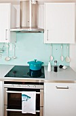 Stainless steel extractor hood above ceramic hob in front of kitchen utensils hanging on glass splashback