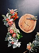 Table centrepiece made from flowers and leaves next to slice of log and secateurs