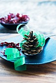 Fir cones and green ribbon used as menu on blue plate
