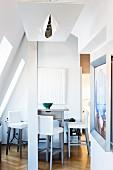 Esstheke mit gepolsterten Barhockern in ausgebautem Dachraum, im Vordergrund zeitgenössische Deckenleuchte