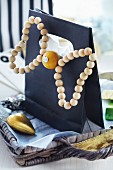 Black gift bag decorated with bow made from wooden beads