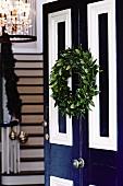 Geöffnete blau-weisse Hauseingangstür dekoriert mit weihnachtlichem Türkranz