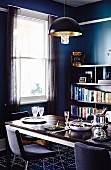 Set table & bookcase in dining room in shades of blue and grey