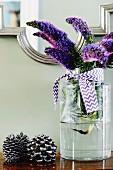 Natternkopfblüten mit blau-weißem Satinband in Glasvase
