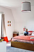 Large bed with red and white bed linen in child's bedroom