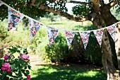 Floral bunting strung between trees in garden