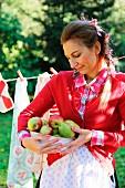 Frau mit geerntetem Obst im spätsommerlichen idyllischen Garten