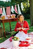 Junge Frau auf Picknickdecke sitzend schält Äpfel, im Hintergrund Tisch mit Einmachgläsern und Wäscheleine