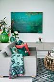 Sofa und Sideboard in Hellgrau, harmonisch mit grünen Accessoires wie Textilien, Glasballon und einem Gemälde kombiniert