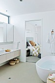 Free-standing bathtub and mirrored cabinet above continuous washstand with drawers next to door of ensuite bathroom with view into bedroom