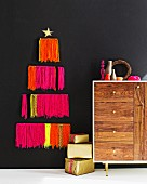 Stylised Christmas tree made from neon woollen fringes on black wall, arrangement of vases on retro sideboard and stacked presents on floor