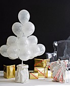 Stylised Christmas tree made from white balloons and presents wrapped in gold paper against black background