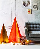 Zwei stilisierte Tannenbäumchen aus Pappe orangefarben und gelbgrün besprüht mit beleuchteter Lichterkette am Boden und grauem Retrosofa