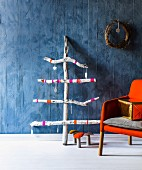 Stylised Christmas tree made from driftwood decorated with stars against blue wall with toadstool ornaments on floor