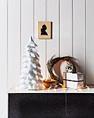 Stylised Christmas tree made from polystyrene cone covered in white ribbon strips, fairy lights and willow wreath on sideboard