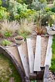 Rustic garden - steps edged with sleepers, white planters on steps, ornamental grasses and shrubs