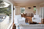 Open-plan interior of country house - armchairs with white loose covers around coffee table, dining area in background and view of furnished wooden terrace through glass wall to one side