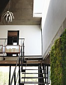Black steel interior staircase and gallery with pendant lamp in natural form; green wall watered with rainwater in foreground