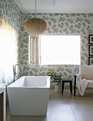 Modern, free-standing bathtub with floor-mounted tape below fluffy pendant lamp in corner of bathroom with floral wallpaper and open window with folding interior shutter