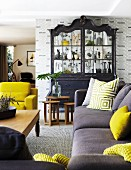 Sofa with bright yellow and patterned scatter cushions in front of rustic wooden coffee table, black-painted dresser with glass doors against patterned wallpaper