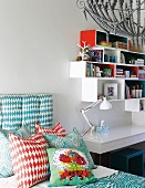 Variously patterned scatter cushions on bed next to table lamp on white desk below white and red shelving modules on wall