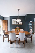 Chairs with white upholstery and wooden table in dining area with concrete floor