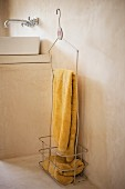 Yellow towels in vintage metal locker basket with hook against pale grey concrete wall; white sink and wall-mounted sink in background on masonry base unit