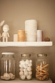 Reels of thread and storage jars on white shelves on sand-coloured wall