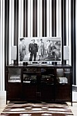 Black, half-height hifi cabinet with flatscreen TV against wall with elegant, black and white striped wallpaper