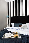 Breakfast tray on black bedspread on bed with black headboard against wall with elegant, striped black and white wallpaper