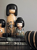Various, painted wooden Kokeshi dolls on stacked books