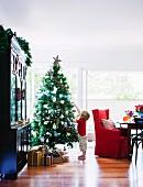 Kleiner Junge bestaunt Stern am Weihnachtsbaum