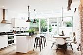 Moderner offener Wohnraum mit Sichtmauerwerk - Essbereich mit Küche vor Terrassentür