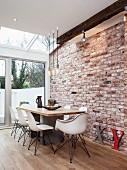 weiße Schalenstühle an Esstisch auf Dielenboden vor Sichtmauerwerk mit moderner Wintergartenverglasung
