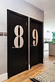 Enormous numbers on black-painted doors in open-plan hallway