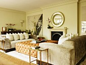 Pale sofa set with arranged scatter cushions and leather-covered ottoman in front of open fireplace in grand living room