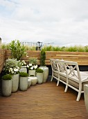 Ceramic planters of pale flowers in corner of roof terrace next to white, traditional bench on wooden floor