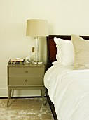 Table lamp on grey-painted bedside cabinet on shimmering rug next to bed with white bed linen